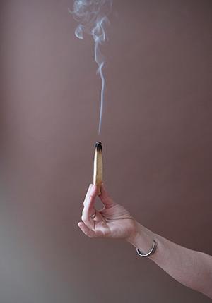 Smoke rises from smudge stick